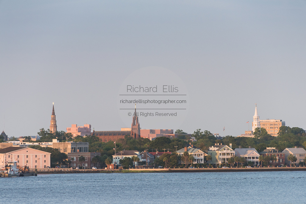 Church steeples and city skyline along the Ashley River at sunset in Charleston, South Carolina.
