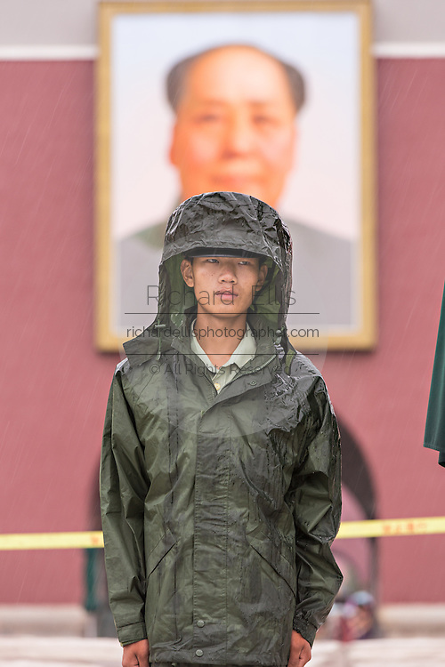 A People's Liberation Army guard stands under the portrait of Mao at the Gate of Heavenly Peace during a rainy summer day in Beijing, China