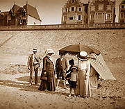 A French family group gathers on a beach in France, during summer. Circa 1900