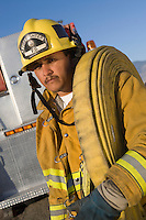 Portrait of firefighter carrying hose