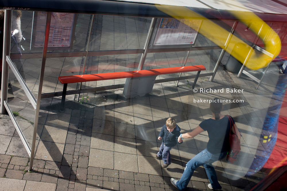 Mother and active child with aerial view of bus stop shadows and reflections.