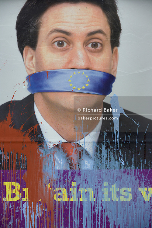 Splashed paint drips down an  anti-EU membership 'UK Independence Party's (UKIP) political billboard showing Labour party leader Ed Milliband silent against a bullying European Union, seen in East Dulwich - a relatively affluent district of south London. The ad is displayed before European elections on 22nd May.