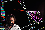Alan Weinstein from the Stanford Linear Collider (SLC) experiment, seen with a computer-simulated collision event between an electron and a positron. The SLC produces Z-zero particles by this collision process, which takes place at energies high enough for the electron and positron to annihilate one another, the Z-zero left decaying rapidly into another electron/positron pair or a quark/anti-quark pair. The Z-zero is one of the mediators of the weak nuclear force, the force behind radioactive decay, and was discovered at CERN in 1983. The first Z-zero seen at SLC was detected on 11 April 1989. MODEL RELEASED [1988] Menlo Park, California.