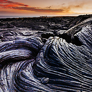 The warm sunset colors of clouds offset with the lines and textures of harded lava in Hawaii Volcanoes National Park.