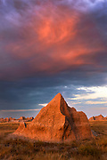 Alpenglow colors the unusual shapes of eroded landscape features in the Badlands National Park in South Dakota, USA. Most of the visible geological features at higher elevations are from the Sharps Formation, which are the youngest and contain a high content of wind-blown ash from volcanic activity to the west.