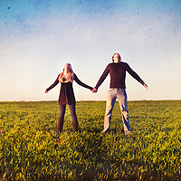 Close up of young woman with blonde hair standing in a field looking upwards holding hands with young man