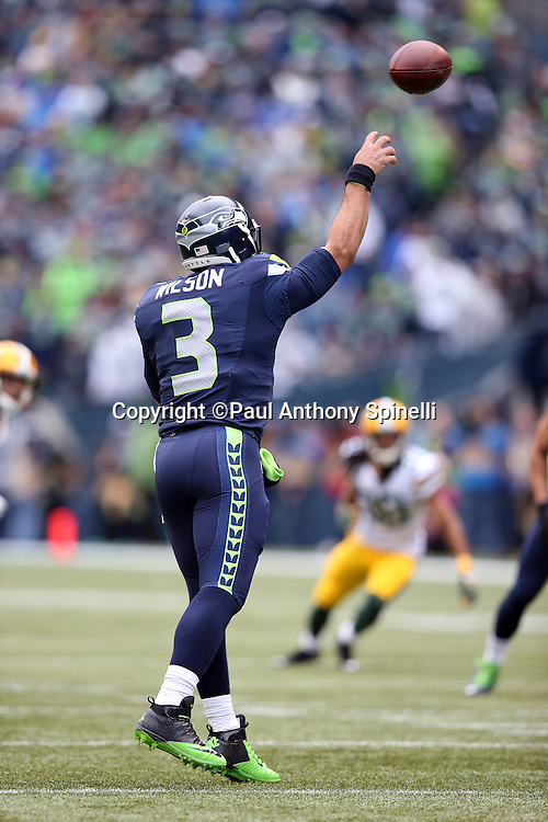 Seattle Seahawks quarterback Russell Wilson (3) throws a third quarter pass for a first down during the NFL week 20 NFC Championship football game against the Green Bay Packers on Sunday, Jan. 18, 2015 in Seattle. The Seahawks won the game 28-22 in overtime. ©Paul Anthony Spinelli