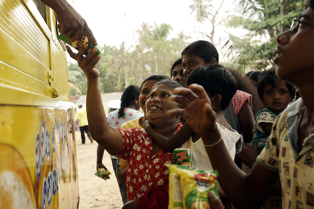 People in the tsunami-devastated town of Galle, on the south-west coast of Sri Lanka, receive packeted food and milk from a distribution truck sent by an international confectionary company on January 14, 2005..Photo by Darrin Zammit Lupi