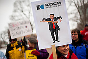 A sign lampoons Gov. Scott Walker's alleged connections with the wealthy Koch brothers during  protests outside the  Wisconsin State Capitol over a bill that threatens to strip collective bargaining rights in Madison, Wisconsin, February 26, 2011. Crowds swelled Saturday as protests enter their 12th day.