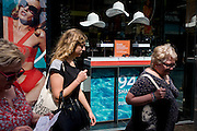Women consumers walk past a sunglasses shop featuring three hats suspended from the store window ceiling.