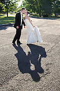 Bride and groom kissing on their wedding day with late day shadow on the ground, East Syracuse, NY