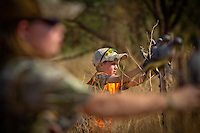 BROTHER AND SISTER WEARING REALTREE CAMOUFLAGE AND BLAZE ORANGE PUTTING DOVE DECOYS ON A BARBED WIRE FENCE