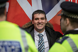 © Licensed to London News Pictures. 05/12/2016. London, UK. A pro-Brexit protester stands between police draped in the Union Jack flag outside the Supreme Court in Westminster. The Supreme Court hearing of the Government's appeal against an earlier High Court decision which ruled that Parliament must give consent before Brexit negotiations can begin. Photo credit: Rob Pinney/LNP