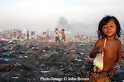 "A young girl has a refreshment to quench her thirst at The Stung Meanchey Landfill in Phnom Penh, Cambodia. She is among the 600 children who work at the site daily. The landfill, known as ""Smokey Mountain"", is a major source of air pollution that impacts the surrounding environment."