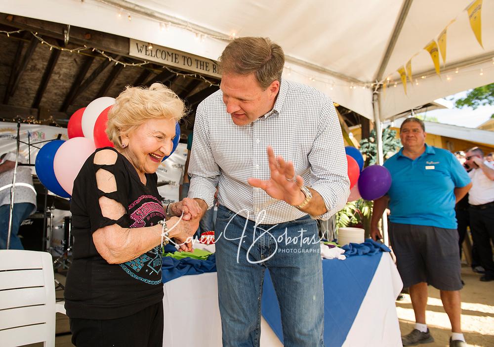 Hope Makris shares a moment with Governor Chris Sununu during the 96th cake cutting celebration at the Naswa Beach Bar Wednesday evening.  (Karen Bobotas/for the Laconia Daily Sun)