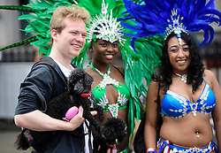 © Licensed to London News Pictures. 29/08/2016. London, UK. A member of the public poses with his dogs and two carnival goers in costume at day two of the Notting Hill carnival, the second largest street festival in the world after the Rio Carnival in Brazil, attracting over 1 million people to the streets of West London.  Photo credit: Ben Cawthra/LNP