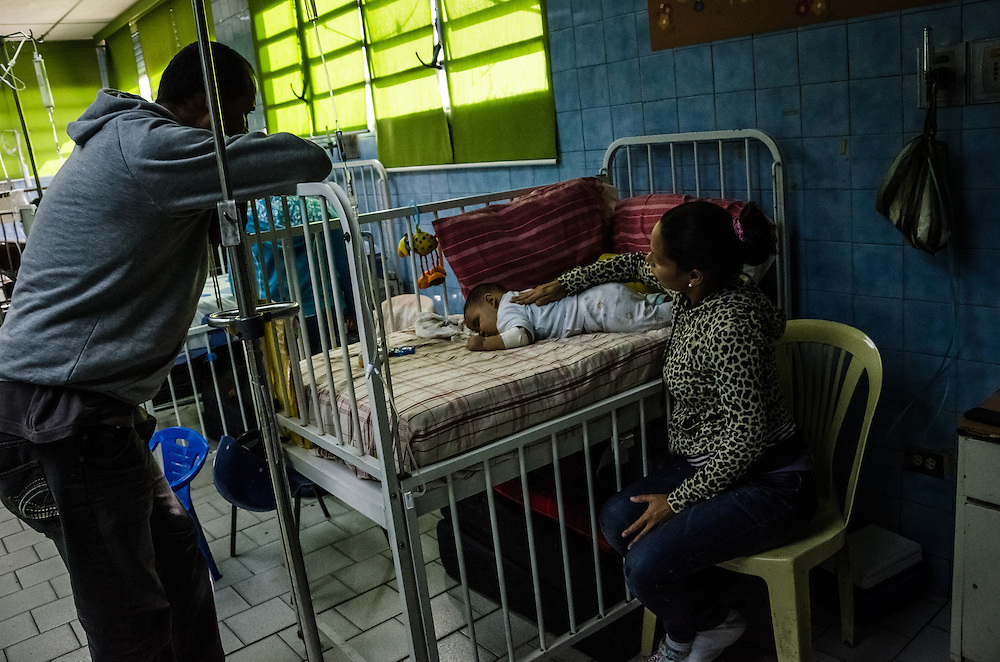 CARACAS, VENEZUELA - JANUARY 21, 2015: Parents look after their 5-month old baby in the pediatric ward of a state hospital in the Petare slum in Caracas.  Despite being a petro-state with one of the largest oil reserves in the world, basic and advanced medical supplies from gauze and surgical gloves, to heart stints, are difficult to find in hospitals and pharmacies across Venezuela.