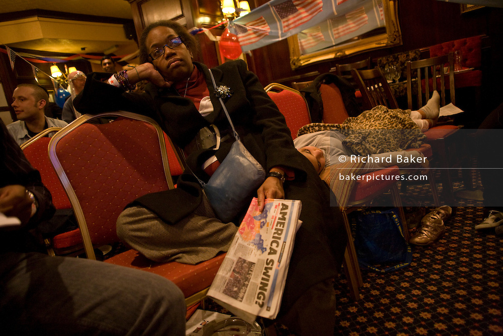 Tired African-American lady listens with sleeping dughter to latest news during overnight election night in London