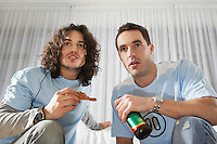Two men watching television having pizza and beer low angle view