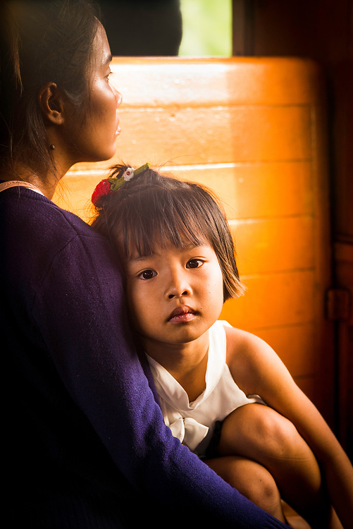 Child in mothers arms sits waiting for the train to arrive at the station in Northern Thailand