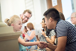 """1 July 2018, Geneva, Switzerland: 6-year old Heidi greets LWF Council member Johanan-Celine Valeriano. On Sunday, LWF Council members joined local congregants for Sunday service at the Evangelical Lutheran Church in Geneva. The 2018 LWF Council meeting takes place in Geneva from 27 June - 2 July. The theme of the Council  is """"Freely you have received, freely give"""" (Matthew 10:8, NIV). The LWF Council meets yearly and is the highest authority of the LWF between assemblies. It consists of the President, the Chairperson of the Finance Committee, and 48 members from LWF member churches in seven regions."""