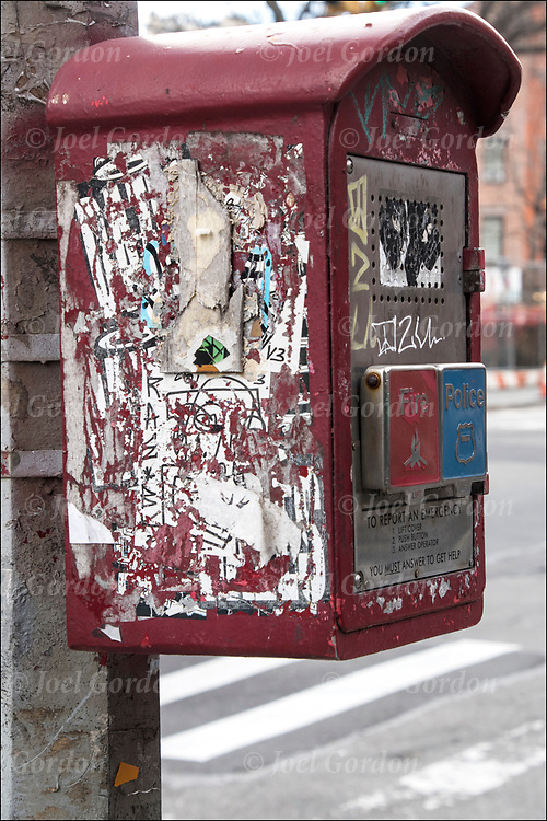 Graffiti street art on side of red fire alarm call box on street in Manhattan.<br /> <br /> Sticker art (also known as sticker bombing, sticker slapping, slap tagging, and sticker tagging) is a form of street art in which an image or message is publicly displayed using stickers. <br /> <br /> These stickers may promote a political agenda, comment on a policy or issue, or comprise a subcategory of graffiti.<br /> <br /> Sticker artists use a variety of label types, including inexpensively purchased and free stickers, such as the United States Postal Service's Label 228 or name tag.<br /> <br /> A fire alarm box, fire alarm call box, or fire alarm pull box is a device used for notifying a fire department of a fire.