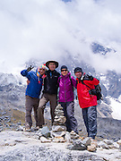 A group of hikers and their guides celebrates their achieving their arrival at Salkantay Pass, along Camino Salkantay, near Soraypampa, Peru, with Montaña Salkantary in the background.