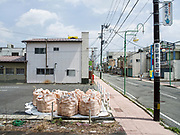 Sacks containing radiation-contaminated foliage and other debris sit by the side of the street in Tomioka, Japan. Tomioka is a ghost town near which an interim storage facility has been built for radiation-contaminated material with hundreds of thousands of sacks piled throughout the area.