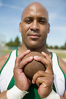 Male shot putter gripping shot, portrait