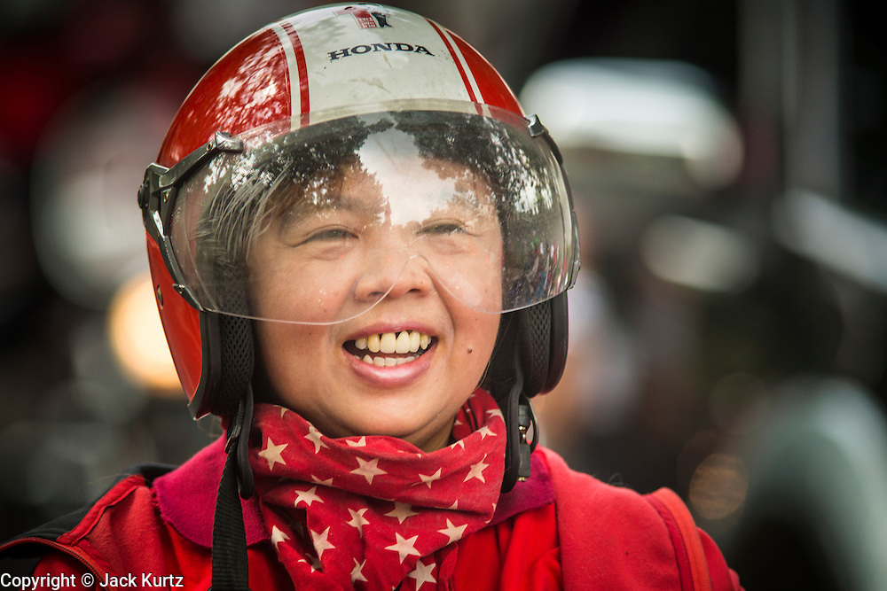"""10 DECEMBER 2012 - BANGKOK, THAILAND:  A smiling Red Shirt on a motorcycle in Bangkok Monday. The Thai government announced on Monday, which is Constitution Day in Thailand, that will speed up its campaign to write a new charter. December 10 marks passage of the first permanent constitution in 1932 and Thailand's transition from an absolute monarchy to a constitutional monarchy. Several thousand """"Red Shirts,"""" supporters of ousted and exiled Prime Minister Thaksin Shinawatra, motorcaded through the city, stopping at government offices and the offices of the Pheu Thai ruling party to present demands for a new charter.        PHOTO BY JACK KURTZ"""