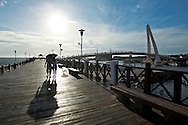 A couple walks into the sunset at Fisherman's Wharf ?????? and Lover's Bridge in Danshui, Taiwan.