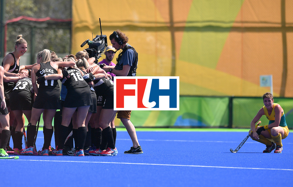 Australia's Kathryn Slattery (R) croaches down as New Zealands's players celebrate at the end of the women's quarterfinal field hockey New Zealand vs Australia match of the Rio 2016 Olympics Games at the Olympic Hockey Centre in Rio de Janeiro on August 15, 2016. / AFP / Carl DE SOUZA        (Photo credit should read CARL DE SOUZA/AFP/Getty Images)