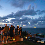 SAN JUAN, PUERTO RICO -- FEBRUARY 3, 2019: <br /> Friends sit on a spot overlooking the La Perla neighborhood  in Old San Juan as the sun goes down and a cruise ship sails away from the city. .  <br /> (Photo by Angel Valentin)