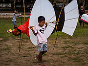 01 AUGUST 2017 - UBUD, BALI, INDONESIA:  A boy carries his janggan (bird shaped) kite off the public school soccer field in Ubud. Kite flying is a popular past time on Bali. It originally had religious connotations, it was used to ask the gods for bountiful rains and harvests. The kites are large. Small ones, flown by individuals are about two meters long, larger ones flown by teams of up to 80 people are ten meters long. There are three shapes of traditional kites, bebean (fish-shaped), janggan (bird-shaped) and pecukan (leaf-shaped). The pecukan is the most unstable and difficult to fly.   PHOTO BY JACK KURTZ