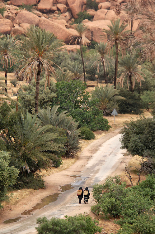 two women walking on road,Palm Avenue, Aguerd Oudad near Tafraoute, Morocco