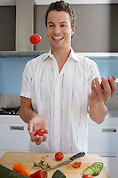 Smiling young man juggling cherry tomatoes in kitchen