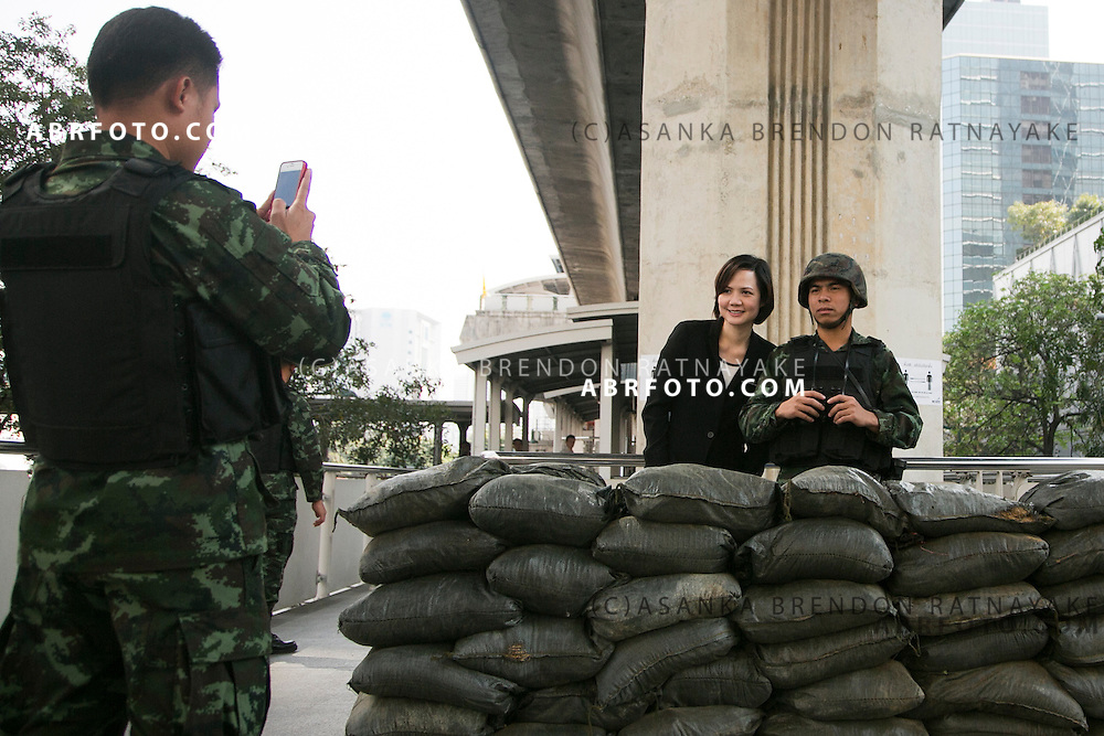 An unarmed Army officer takes a photo of a office worker posing with an Army officer in front of Sandbags positioned at one of the Skyrail stations in Bangkok.