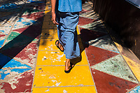 A young Burmese man walks along a colorful foot path in downtown Yangon, Myanmar.