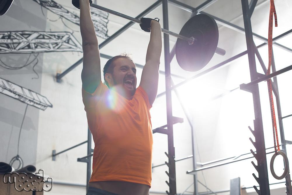 Dedicated man lifting barbell in crossfit gym