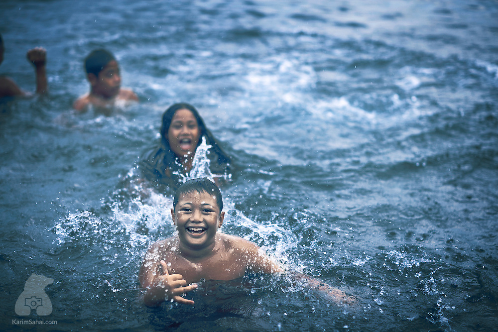 Children swimming in a pool, Savaii island, Samoa.