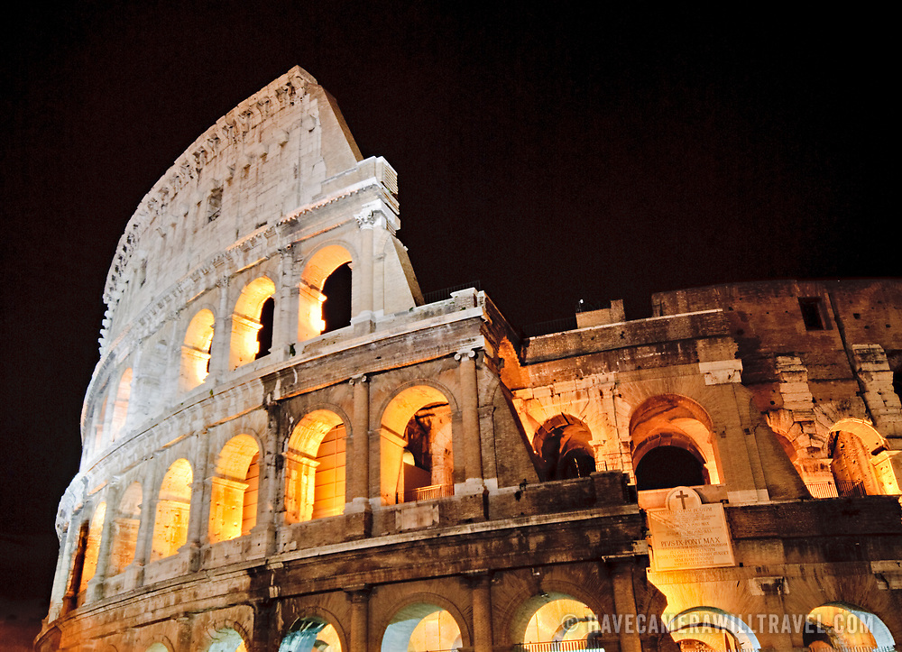 A telephoto shot of part of the famous Coliseum of Rome under lights at night.