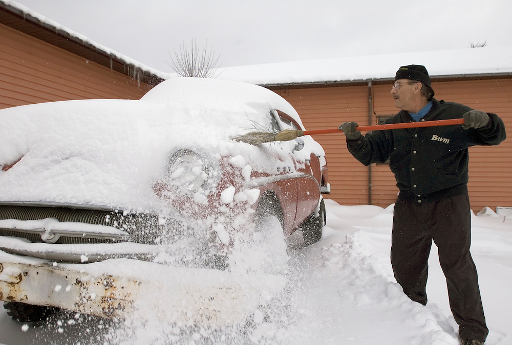 """Jim """"Hoolie"""" DeCaire, owner of """"Da Yooper's Tourist Trap and Museum"""" in Ishpeming, Mich. sweeps snow from a vehicle at the museum."""