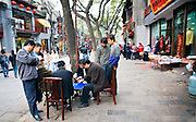 CHINA, BEIJING: Chinese men playing xiangqi or Chinese chess, a traditional Chinese board game of skill and luck, on a street in the old Muslim quarter of Xi'an, as specatators gather to watch.
