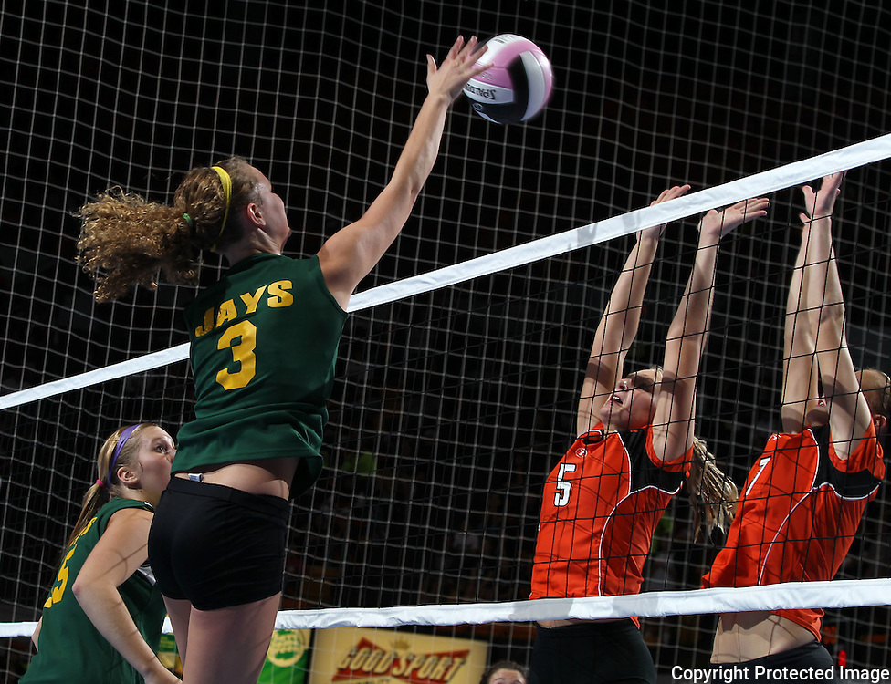 LeMars Gehlen Catholic's Kenzie Kellen (3) gets the ball over Tripoli's Erica Ollendieck (5) and Natalie Figanbaum (7) during their 1A semifinal match in the state volleyball tournament at the U.S. Cellular Center at 370 1st Ave E on Friday evening, November 12, 2010. (Stephen Mally/Freelance)