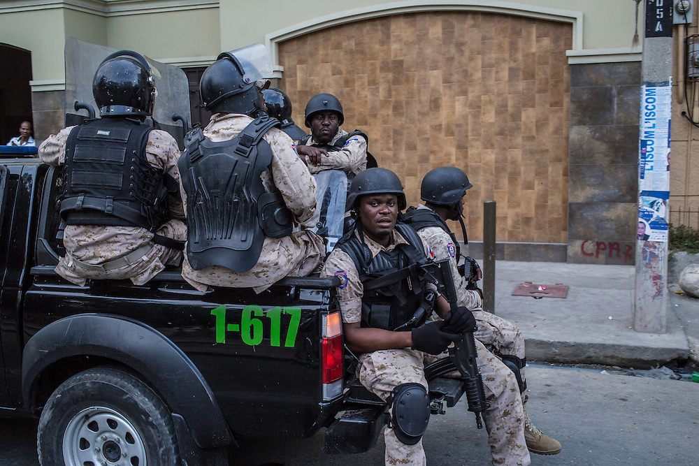 Riot police patrol in a truck against anti-government protesters on Saturday, December 13, 2015 in Port-au-Prince, Haiti. The police have been frequently accused of using excessive force against demonstrators, and on this day one protester, Nicolas Jolin, was alleged to have been shot and killed by police while protesting.