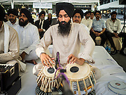 21 AUGUST 2015 - BANGKOK, THAILAND: A Sikh drummer performs during the Sikh prayer service at Central World to honor the dead from the Erawan Shrine bombing. The Bangkok Metropolitan Administration (BMA) held a religious ceremony Friday for the Ratchaprasong bomb victims. The ceremony started with a Brahmin blessing at Erawan Shrine, which was the target of a bombing Monday night. After the blessing people went across the street to the plaza in front of Central World mall for an interfaith religious service. Theravada Buddhists, Mahayana Buddhists, Muslims, Sikhs, Hindus, and Christians participated in the service. Life at the shrine, one of the busiest in Bangkok, is returning to normal. Friday the dancers and musicians who perform at the shrine resumed their schedules.     PHOTO BY JACK KURTZ