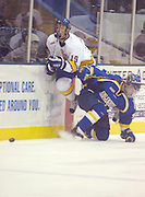 Lake Superior State University's John Scrymgeour (left) jumps over University of Alaska Fairbanks' Joe Sova (right) while chasing the puck into the offensive zone during the second period of the Lakers Friday night 4-3 win over the University of Alaska Fairbanks at Taffy Abel Arena in Sault Ste. Marie.