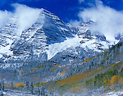 A late Autumn snow storm clears out over the iconic Maroon Bells near Aspen Colorado