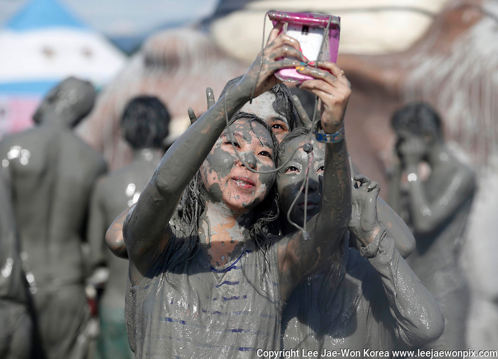 Tourists take pictures with a mobile phone after playing in the mud during the Boryeong Mud Festival at Daecheon beach in Boryeong, about 190 km (118 miles) southwest of Seoul, July 19, 2013. /Lee Jae-Won