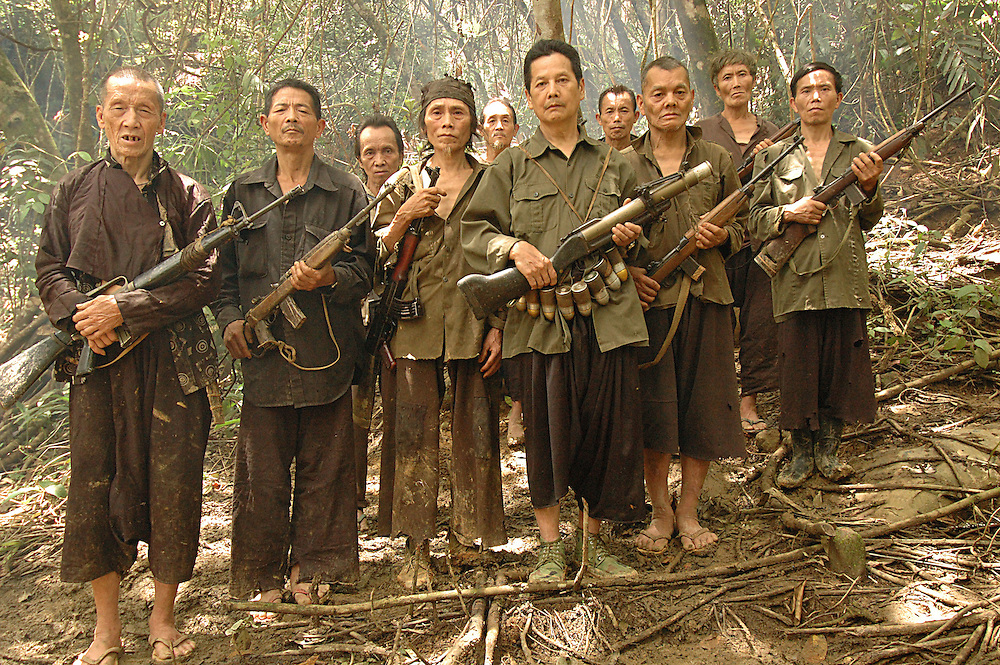 Village leader, Blia Shoua Her (center), holding an old American M-79 grenade launcher and surrounded by former Hmong fighters from the CIA's Secret Army, near Vang Vieng, Laos, July 3, 2006.  Most of the men are from surrounding CIA Lima Sites 363, 319, 90 and 74.  The CIA established remoted jungle landing strips in Laos called Lima Sites to provide aerial supply to their Secret Army.  Ironically the Lao communist government now uses Lima Site 363 to supply its troops and to attack Blia Shoua Her and his men from the Secret Army...**EXCLUSIVE, no tabloids without permission**.The Hmong people pictured have hidden in remote mountains of Laos for more than 30 years, afraid to come out.  At least 12,000 are said to exist, with little food, scavenging in the jungle. Most have not seen the modern world.  Since 1975, under the communists, thousands of reports evidence the Hmong have suffered frequent persecution, torture, mass executions, imprisonment, and possible chemical weapons attacks.  Reports of these atrocities continue to this day.  The Lao Government generally denies the jungle people exist or that any of this is happening.  The Hmong group leader, Blia Shoua Her, says they are not part of the Hmong resistance and want peace.  He claims they are just civilians defending their families, hoping to surrender to the UN..